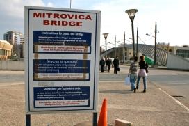 Roadside sign with instructions for cross the Mitrovica Bridge, looking towards the southern side of the city. People approaching each other, heading in opposite direction. Mitrovica, Kosovo.